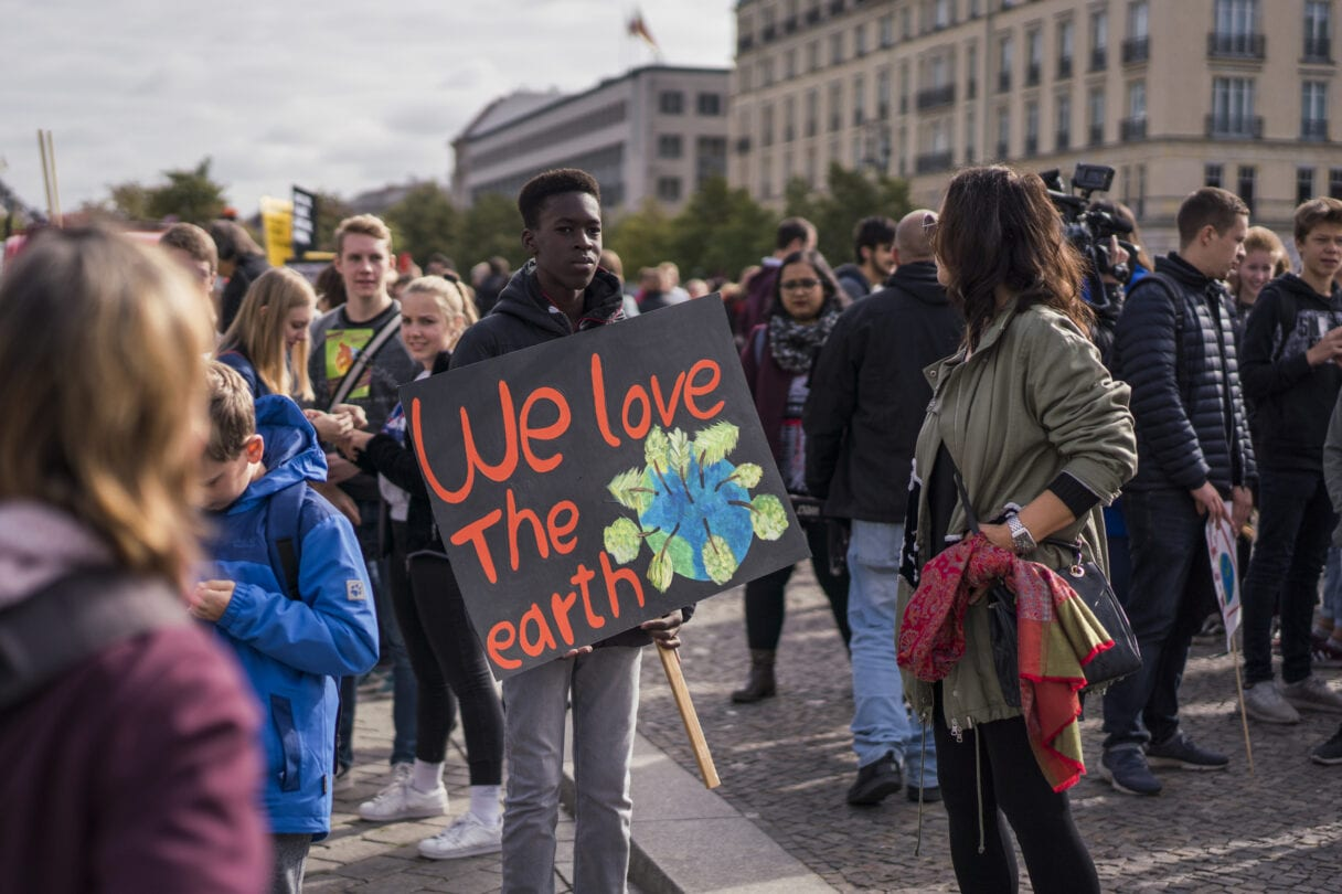 A young man stands in a crowd holding a hand-painted sign saying 'We love the earth'