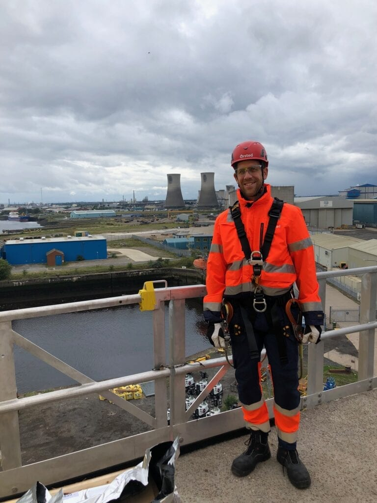 a man standing on a high-up platform with climbing gear on and an industrial zone in the background.
