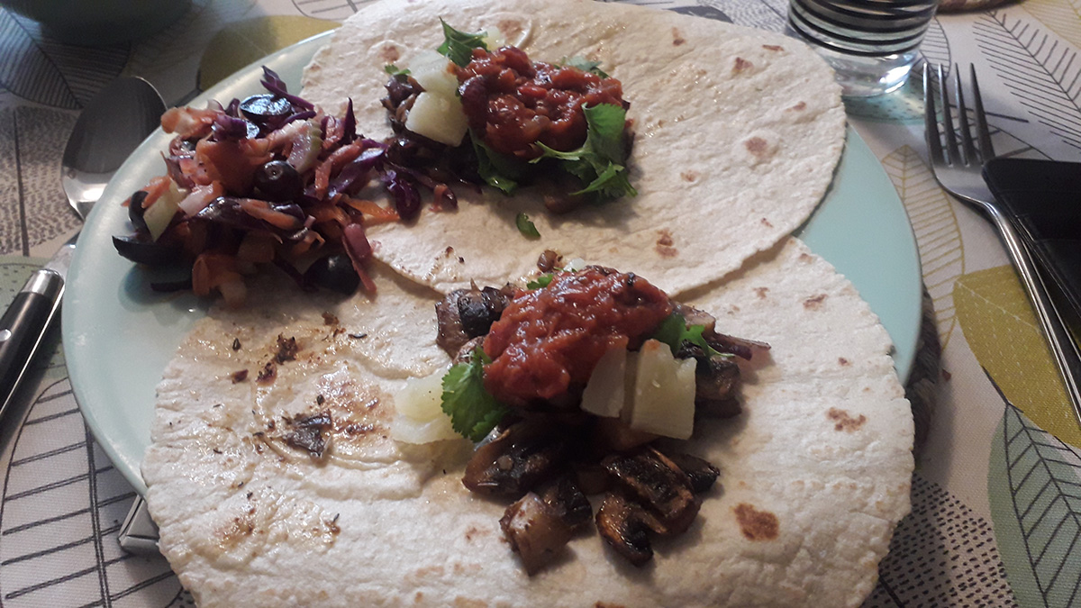 Three tortilla wraps loaded with mushroom taco filling, ready to eat