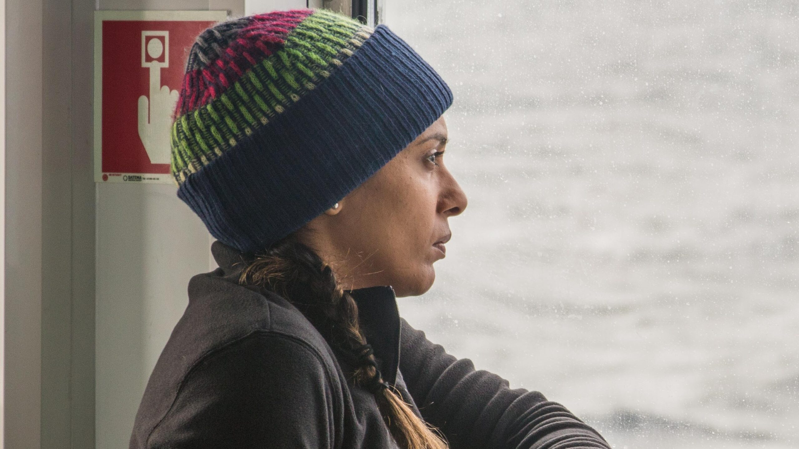 Closeup of Meena on a ship wearing a hat and fleece looking pensively out to sea