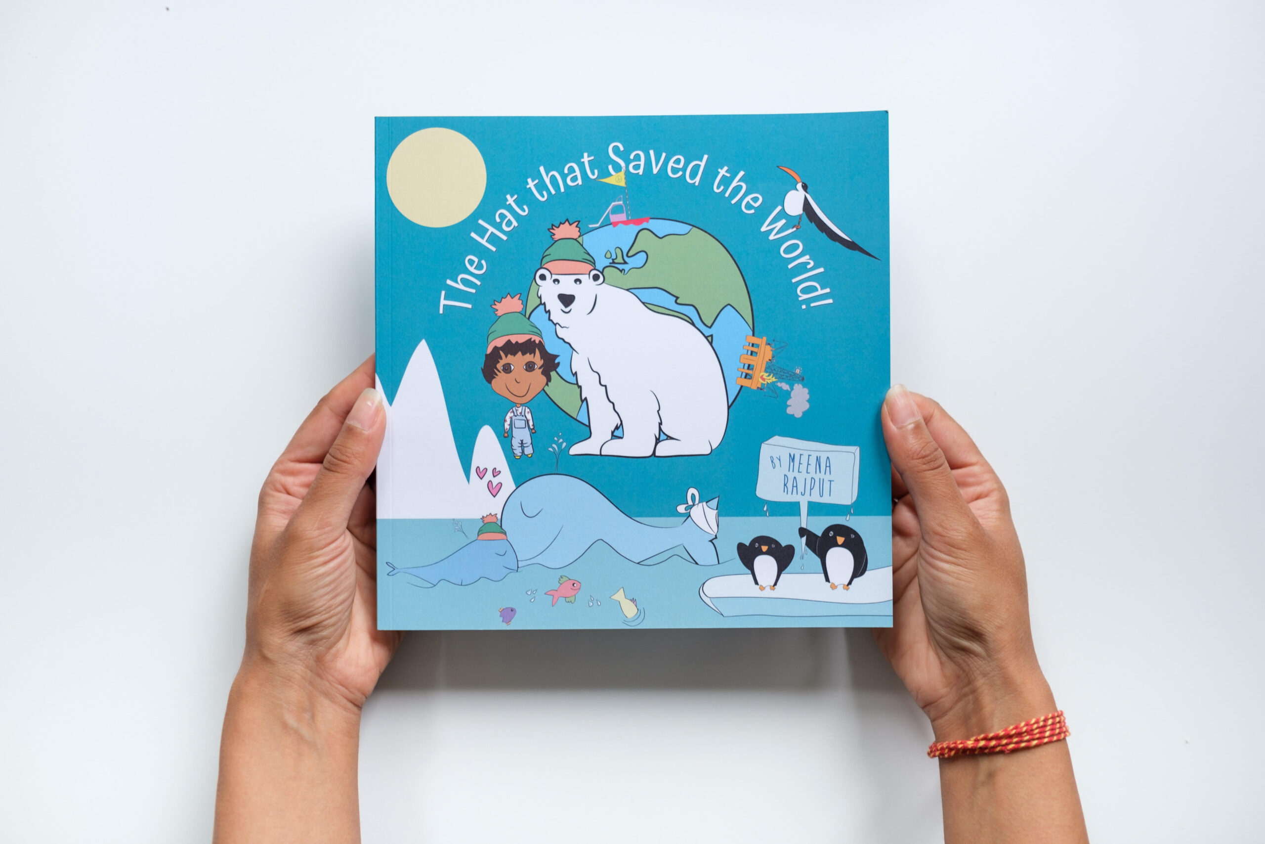 Hands holding a children's book 'The Hat that Saved the World', which features a young child with a polar bear wearing a hat
