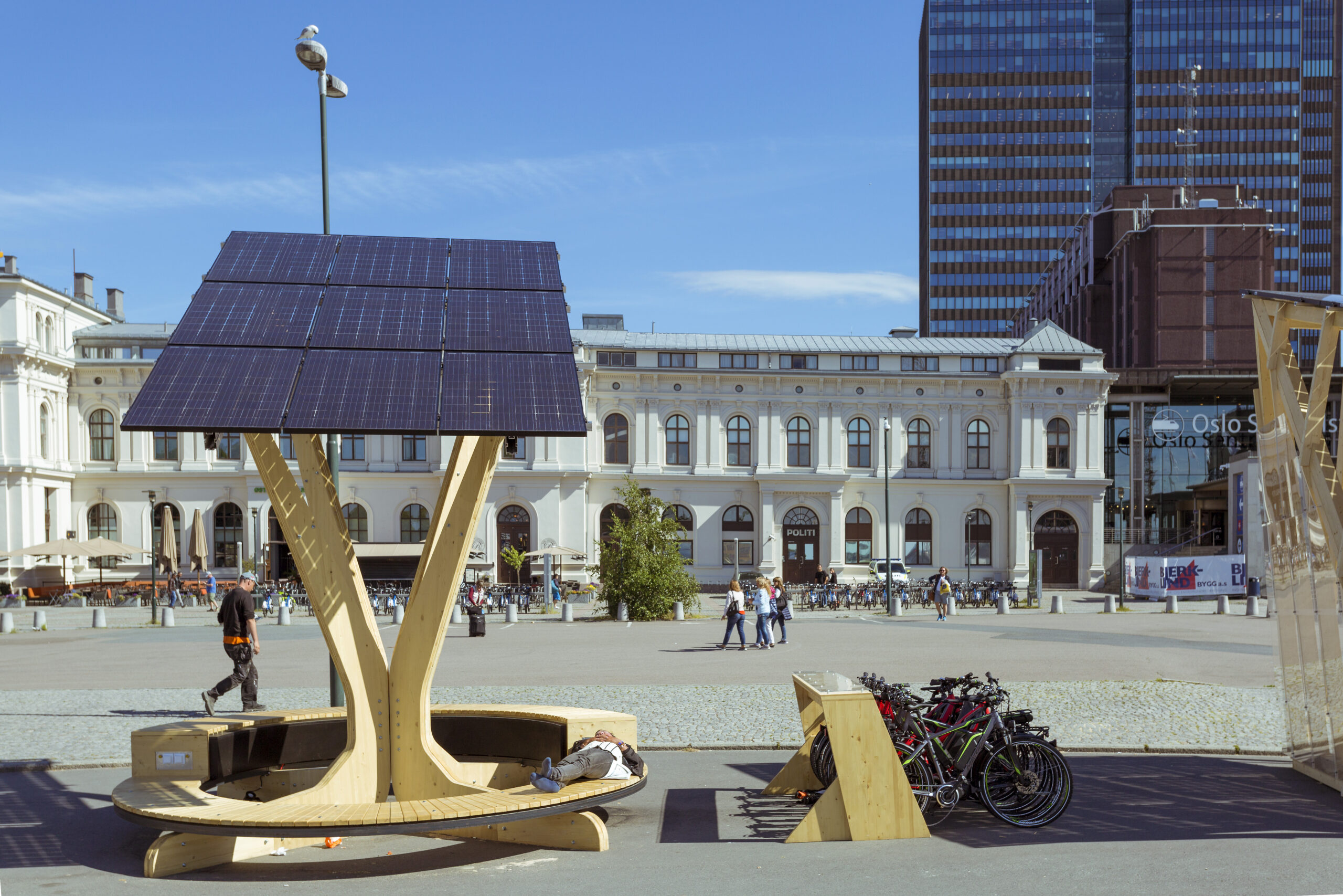 A bright sunny day in Oslo, a view of a wide square with official building in the background, and a bike docking station with a bench covered in a solar panel above it, on which someone is napping.