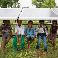 Children sit on the frame underneath a row of solar panels, smiling at the camera