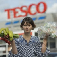 A person stands outside a Tesco superstore holding up fruit and vegetables in one hand and plastic packaging in the other.