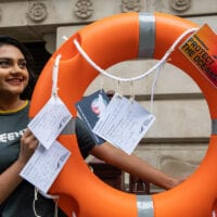 A Greenpeace campaigner holds up a lifebuoy decorated with postcards from people calling on the government to protect the oceans.