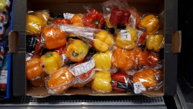 Plastic-wrapped red and yellow peppers on a supermarket display