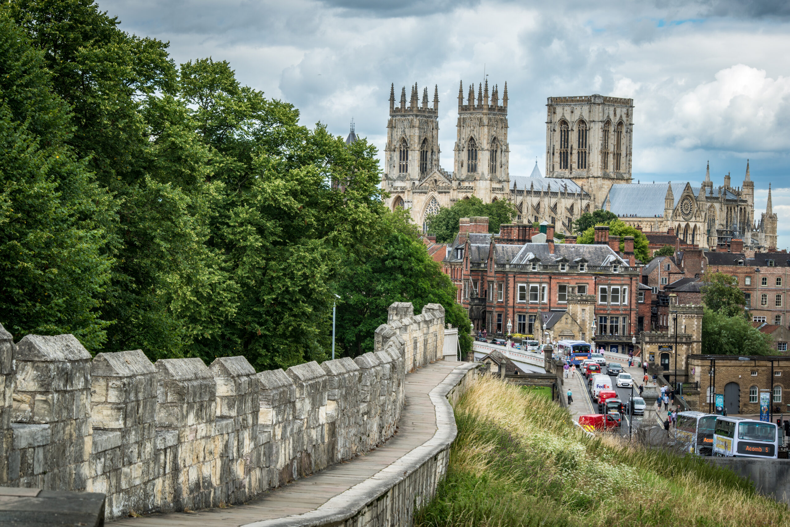 A view of York Minster, with a city wall and a street packed with cars, vans and buses in the foreground.