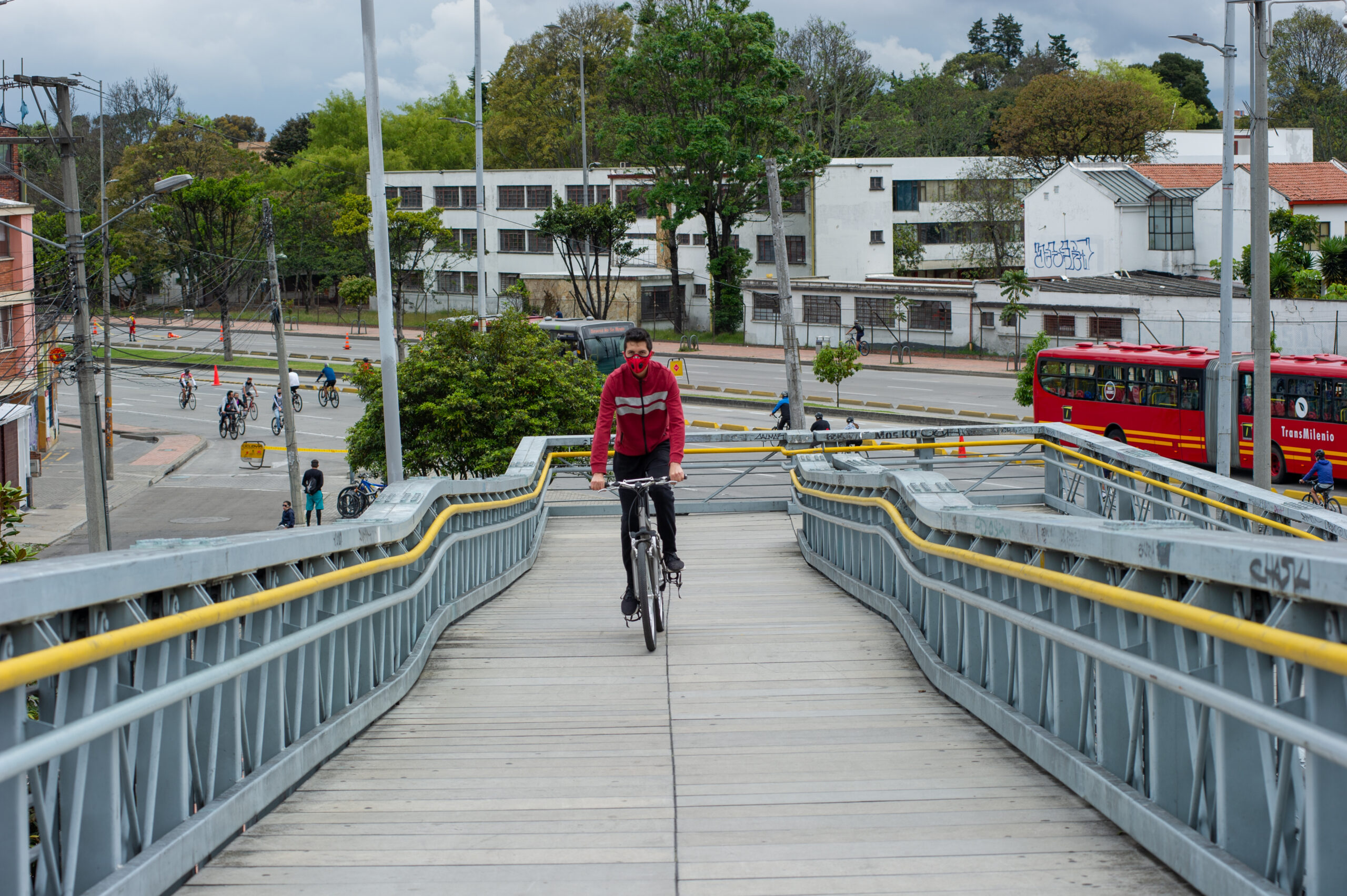 Cyclist climbing a wide bridge designed for cyclists and pedestrians with two levels of handrails and a clear street in the background with a few cyclists and one bus.