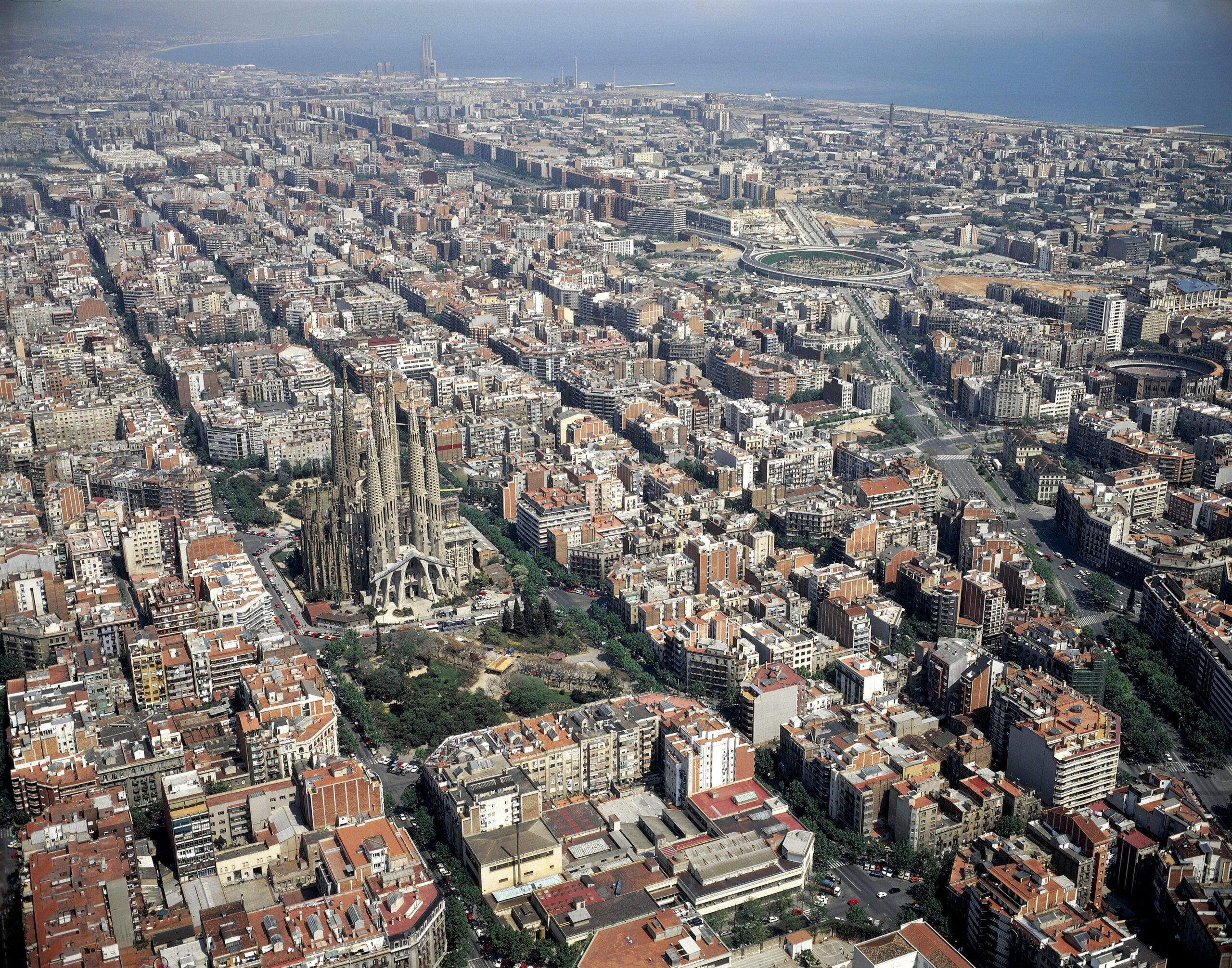 Aerial view of Barcelona from the Eixample district to the sea in the distance, with the Sagrada Familia church in the middle