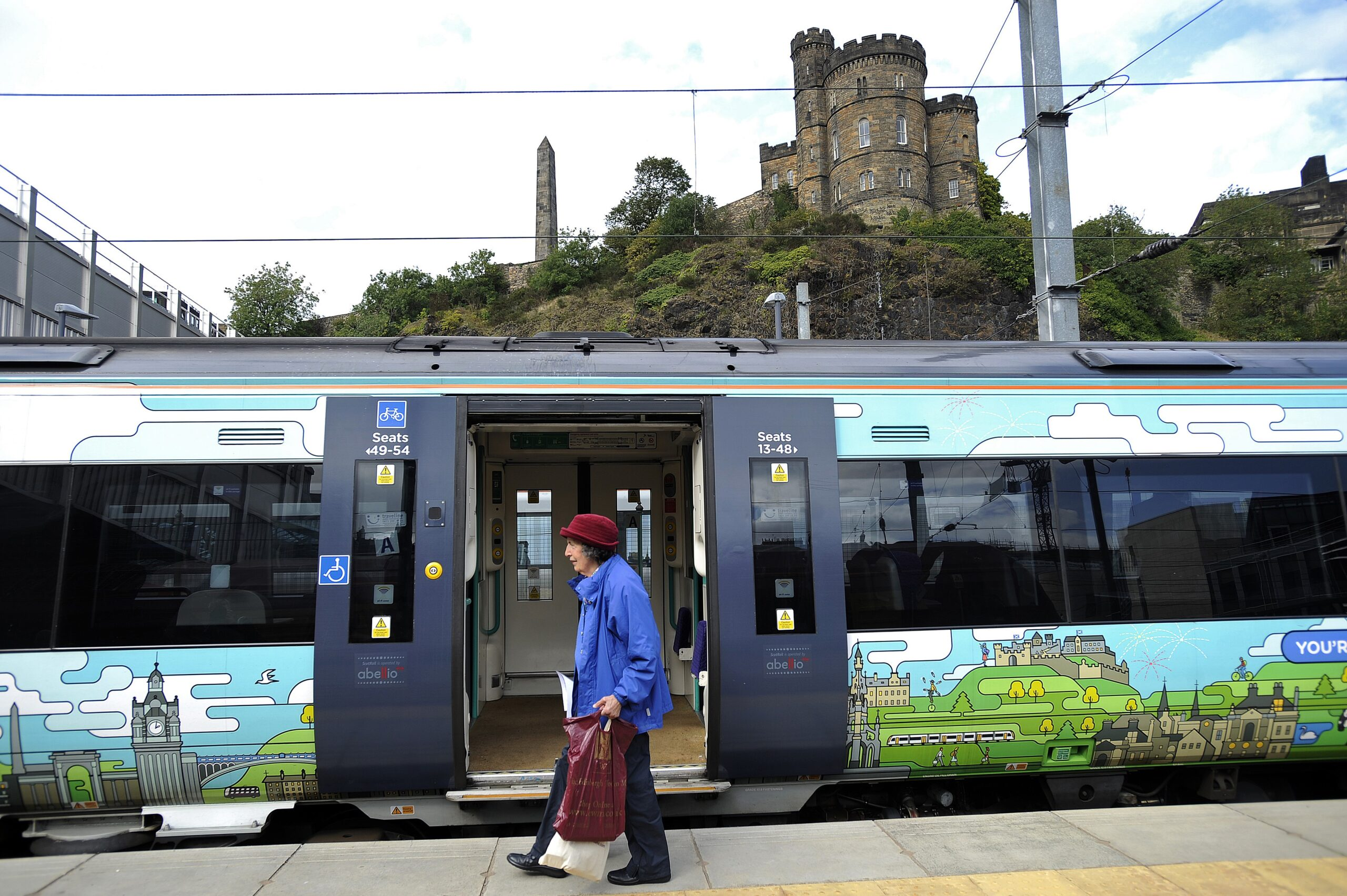 An older woman carrying chopping bags walks past a shiny new train with a castle in the background