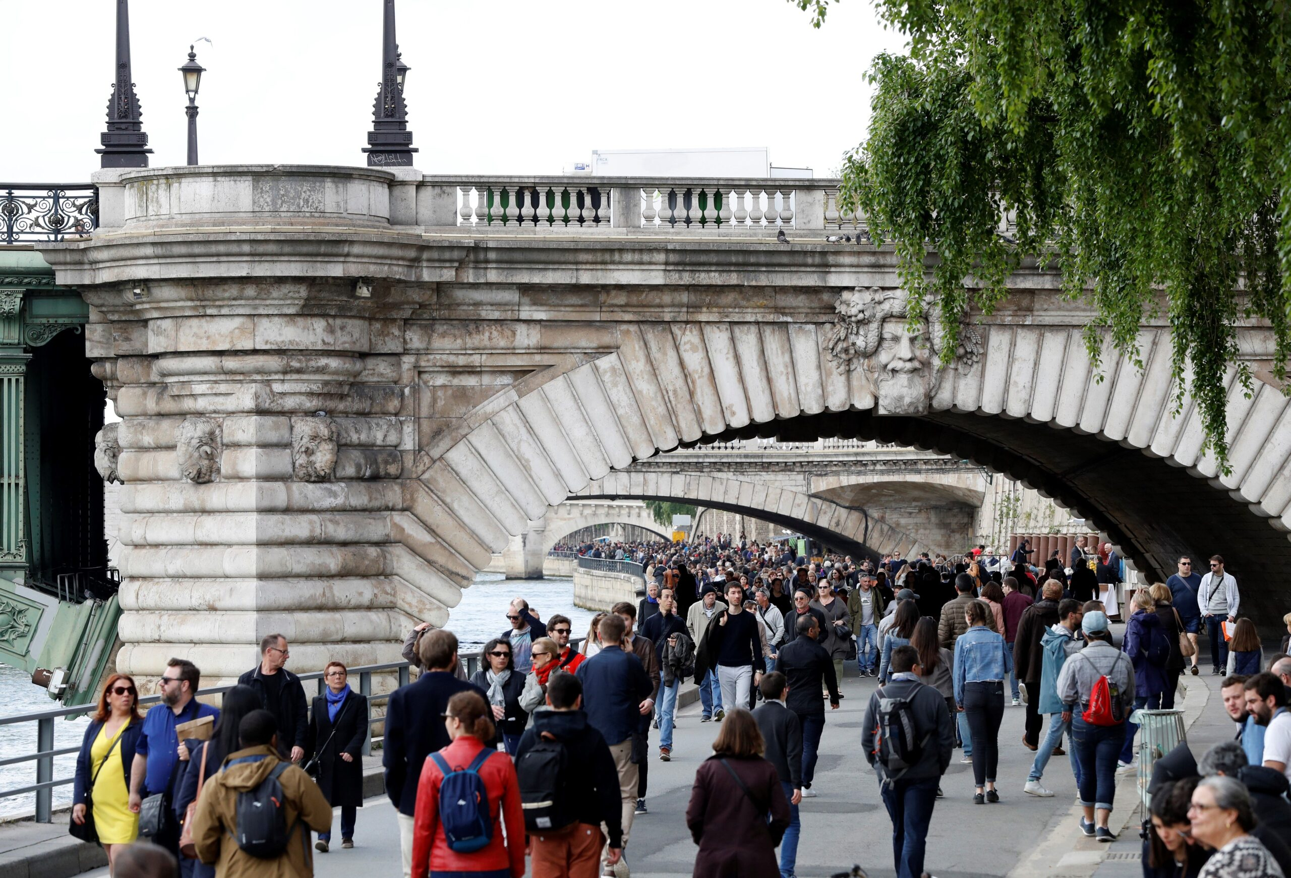 Many people walking along the bank of the River Seine in Paris, on a wide road with the stone arches of multiple bridges over the river in the foreground and distance.