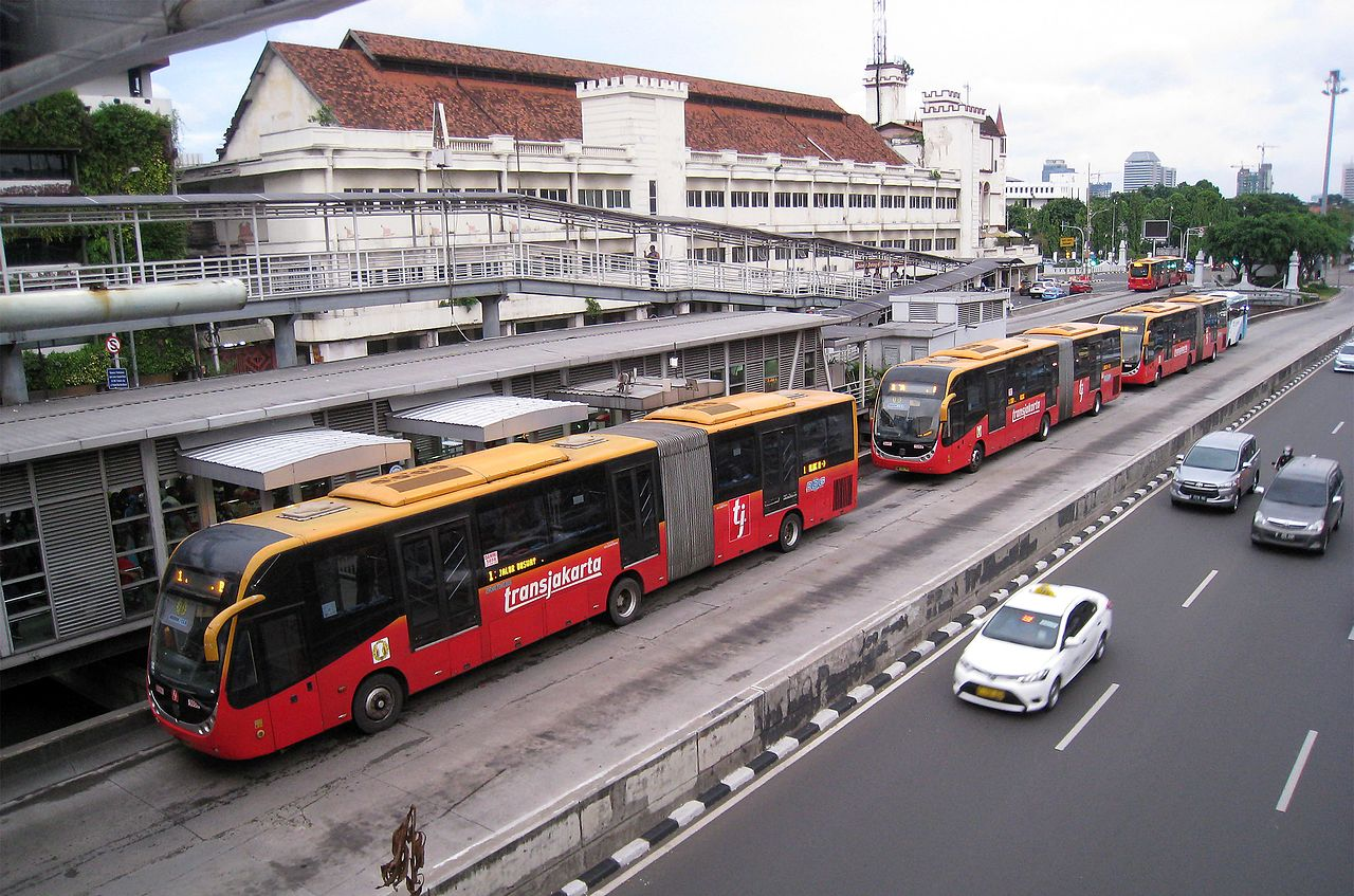 Three red and yellow articulated buses in a separated two lane area stopped to pick up passengers outside a bus terminal featuring multiple buildings and pedestrian bridges, next to a clear road with only four cars.