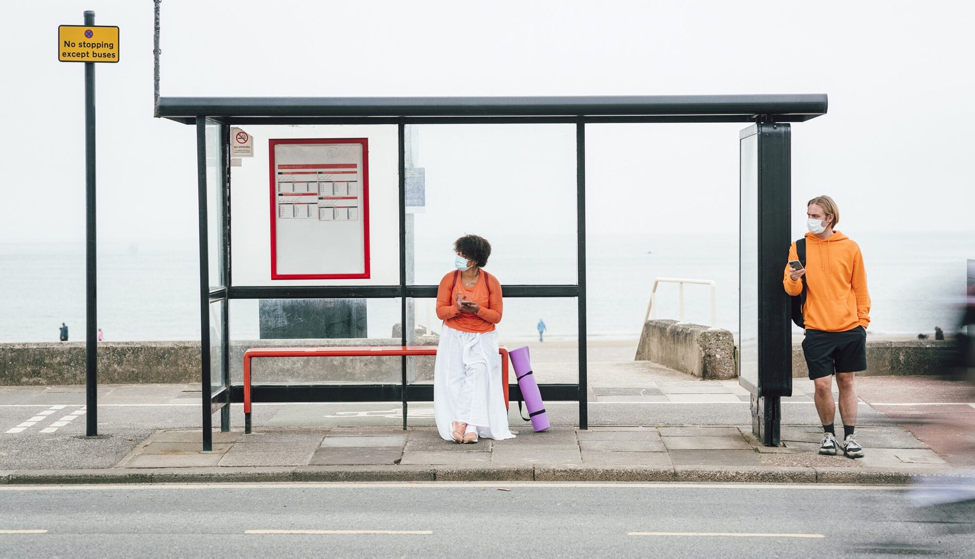 A woman of colour waits at a bus shelter by a road