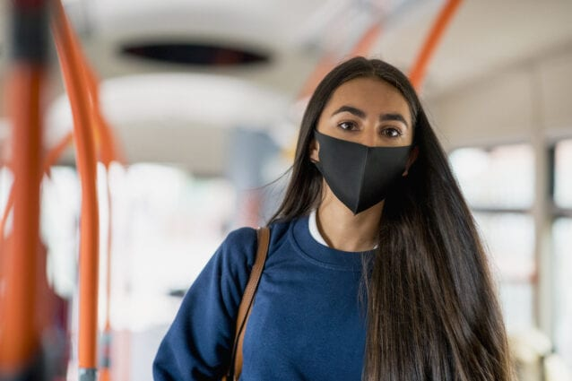 A person of colour wearing a mask and school uniform looking for a seat on a bus