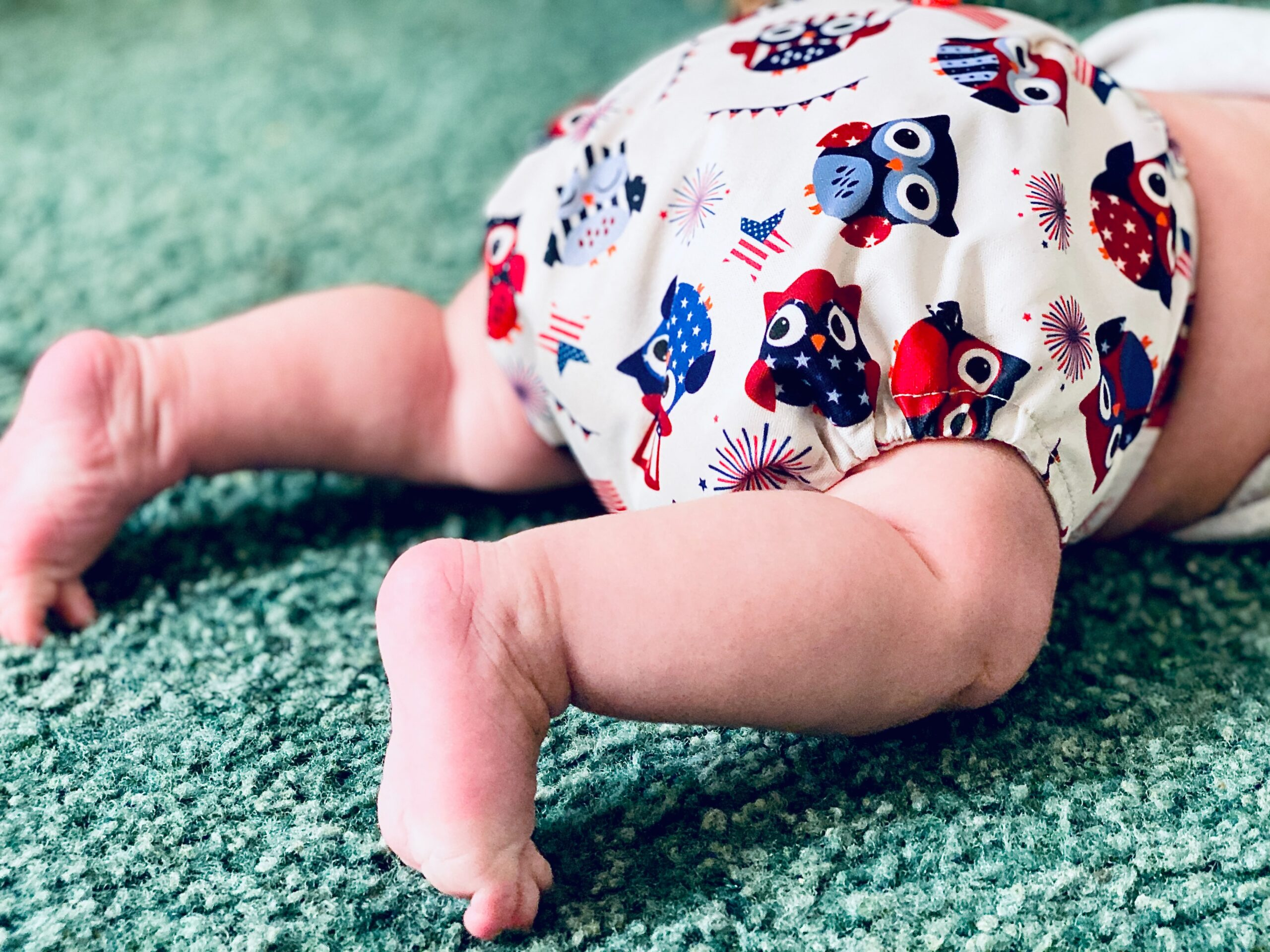 View of a baby's legs lying face down on a green carpet and wearing a reusable nappy