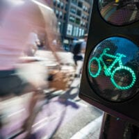 A person on a bike passes a dedicated green light for cycles.
