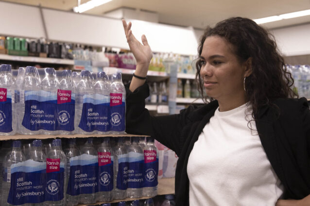 A shopper makes an exasperated gesture towards a head-high stack of plastic-wrapped bottled water multipacks