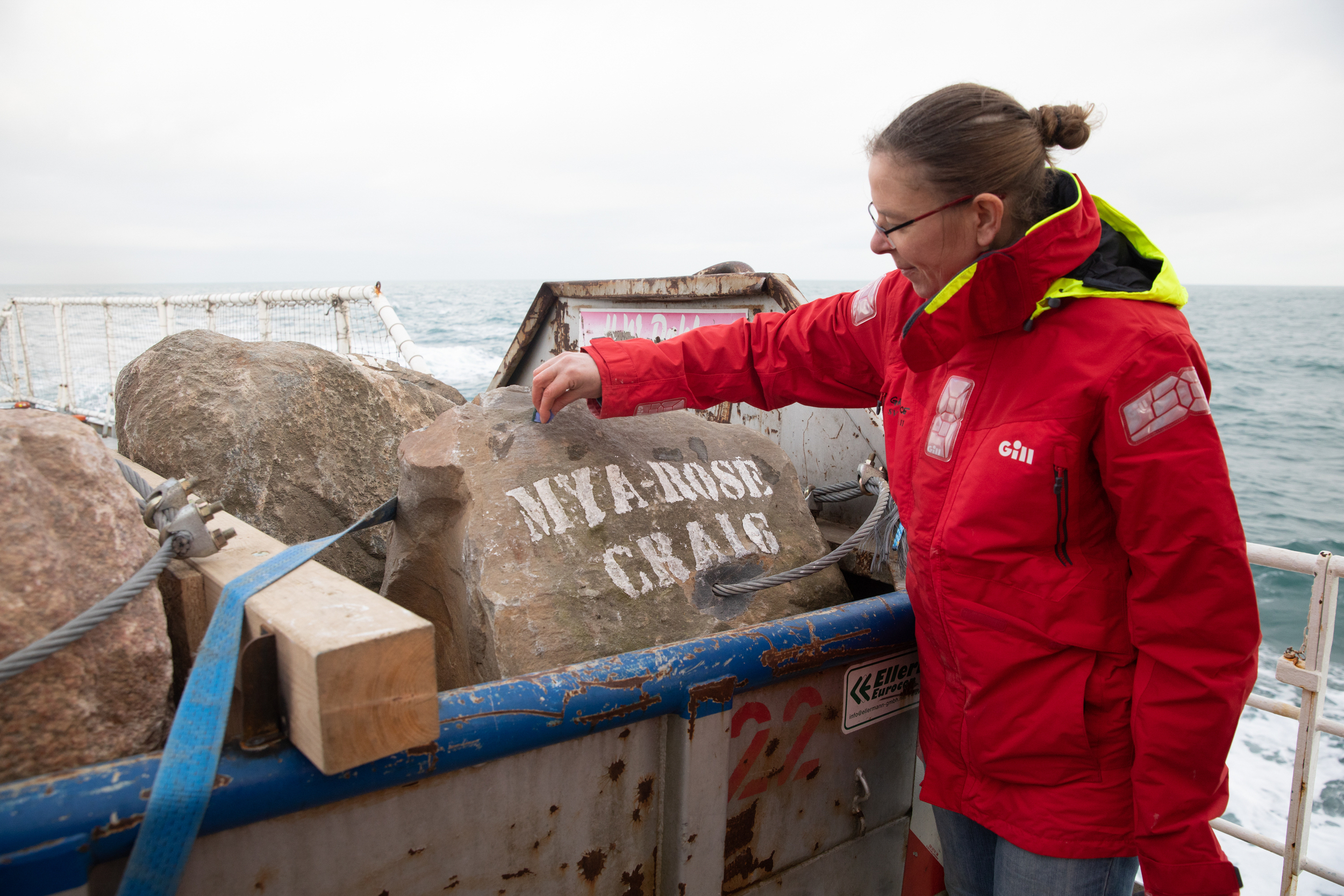 A Greenpeace crew member inspects a large boulder secured on deck, stencilled with the name Mya-Rose Craig