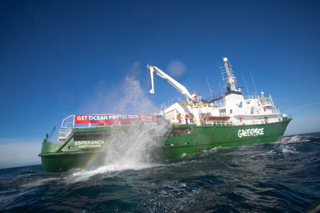 A large splash erupts alongside a Greenpeace ship as a boulder is placed in the water