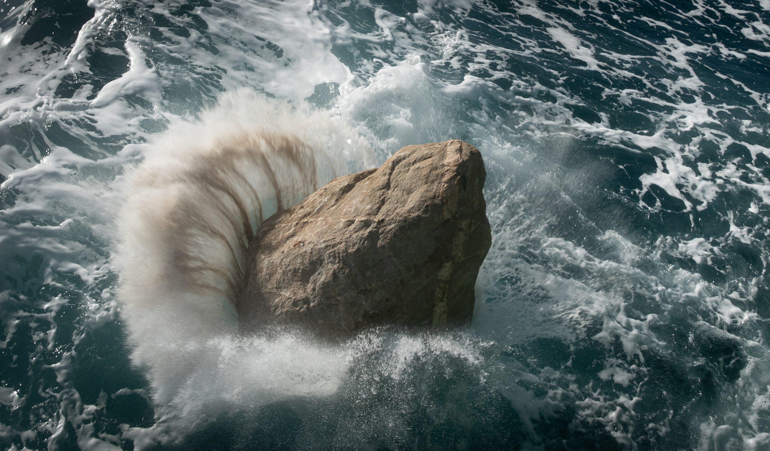 A boulder strikes the surface of the ocean, creating a powerful splash