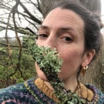 Informal portrait of Hannah Davey holding a stick covered in lichen