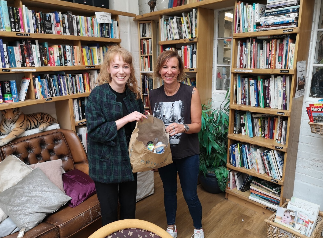 Two people stand in front of a bookcase smiling at the camera and holding a bag of plastic packaging.