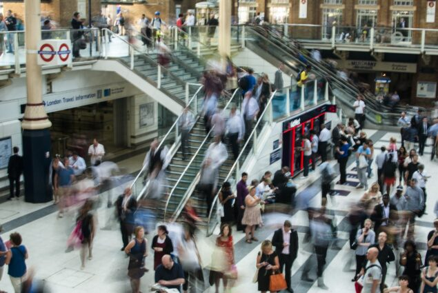A busy station concourse viewed from above. Fast-moving pedestrians are motion-blurred.