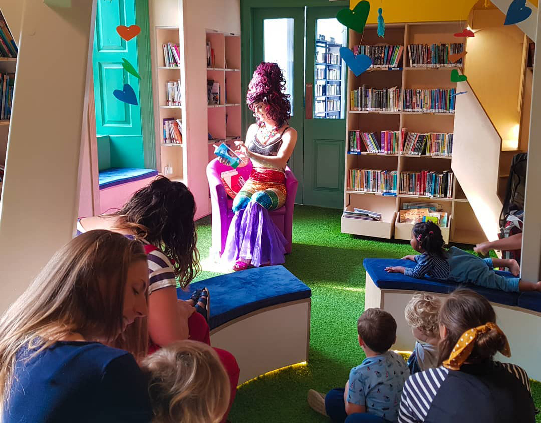 A drag queen reads to a group of children in a colourful sunlit classroom