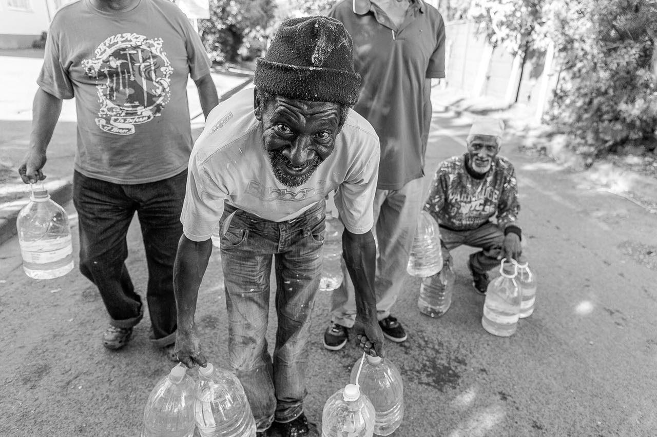 Four Black South African men, one in the foreground and one squatting so their faces show they are of older ages, holding five litre bottles of water to collect water. The men in front are holding at least four bottles, two in each hand, and smiling.