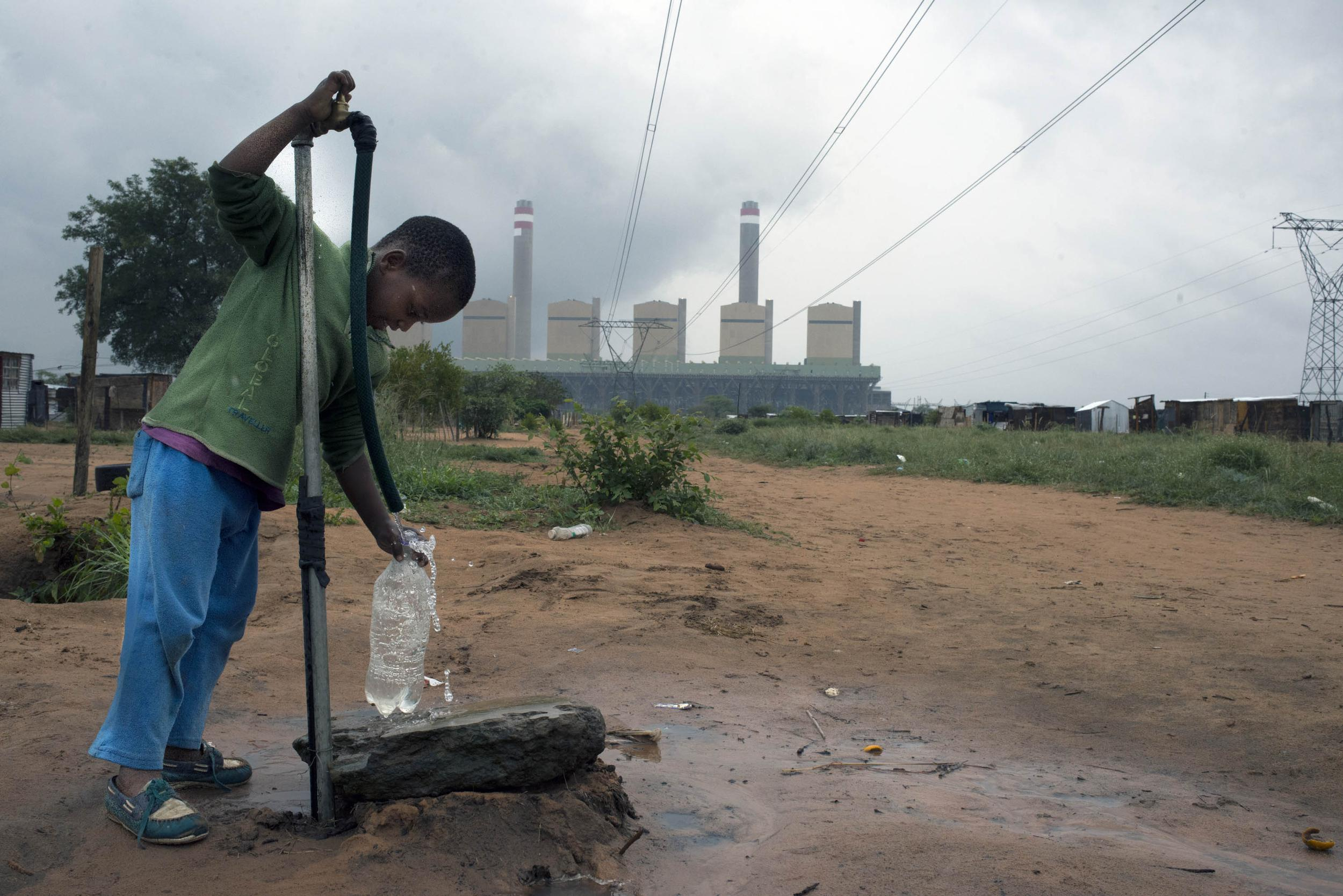 A small boy at a water tap in blue trousers and a green top. The red earth is wet around the tap and the sky is grey, in the background a power station with lines and pylons.