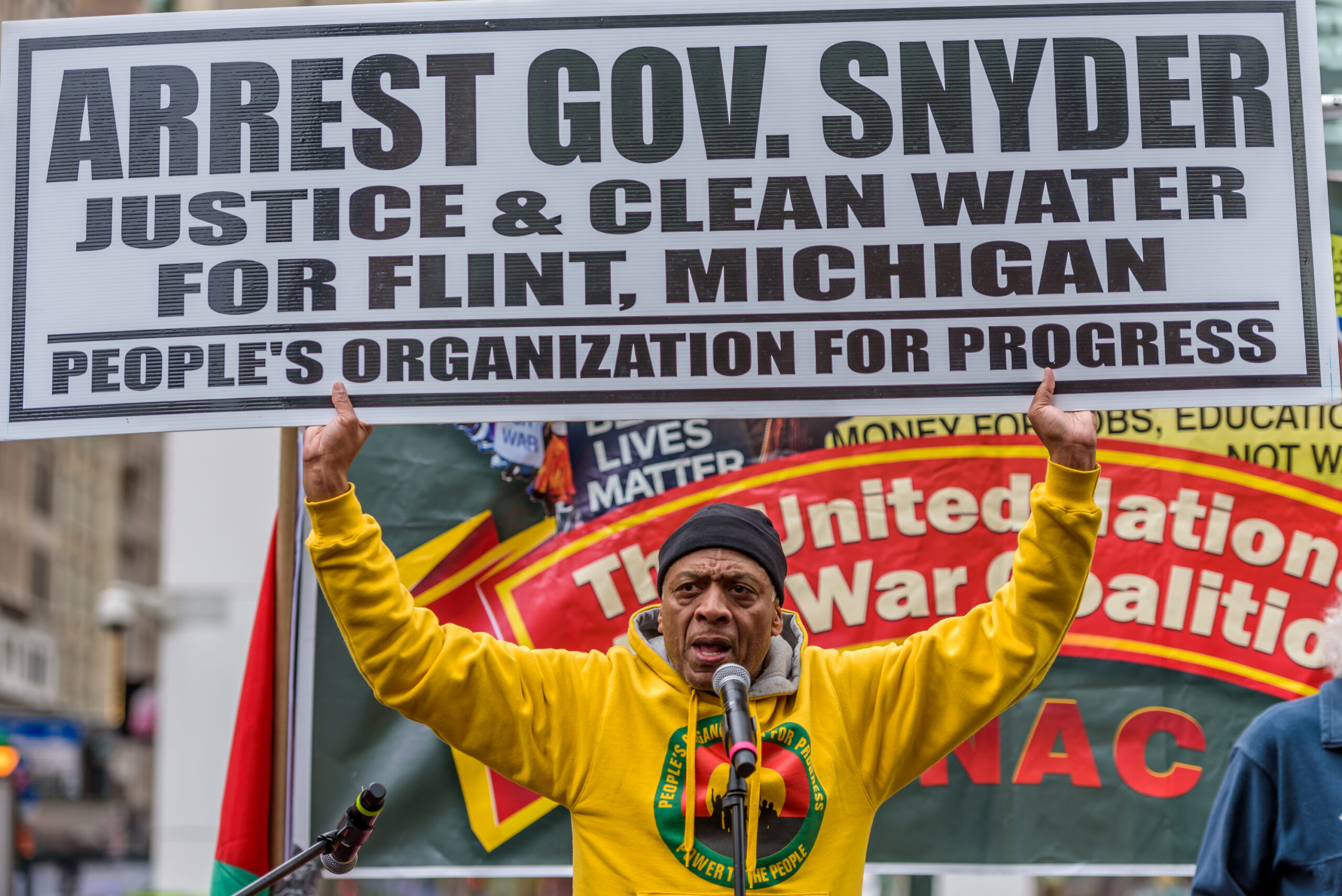 An older black man in a bright yello hoodie with an activist emblem on it holds up a sign saying 'Arrest Gov. Snyder. Justice & Clean Water for Flint, Michigan. People's Organisation for Progress'. He is in front of a banner on which the words 'united' and 'war' can be made out, and a sign saying 'black lives matter'