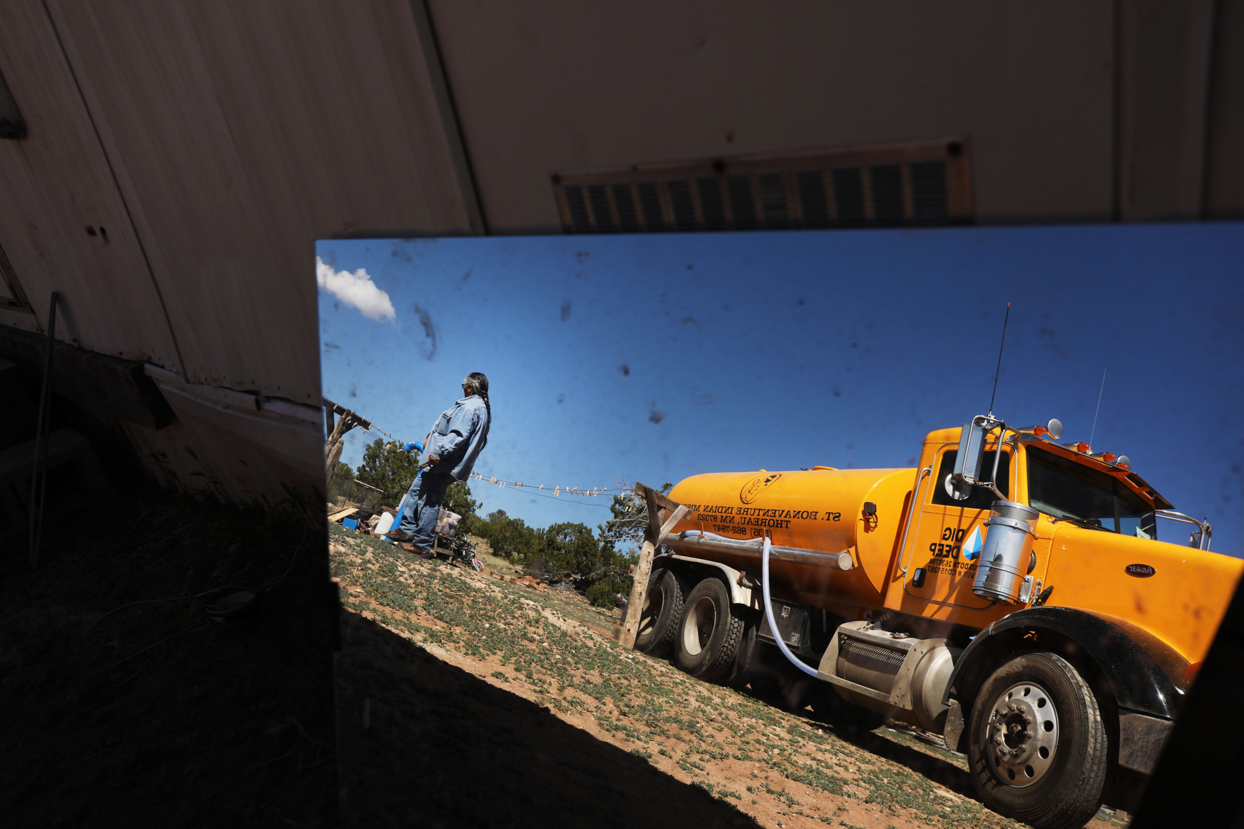 A large yello water truck with its operator reflected in a mirror, delivering water to a household on Navajo land.
