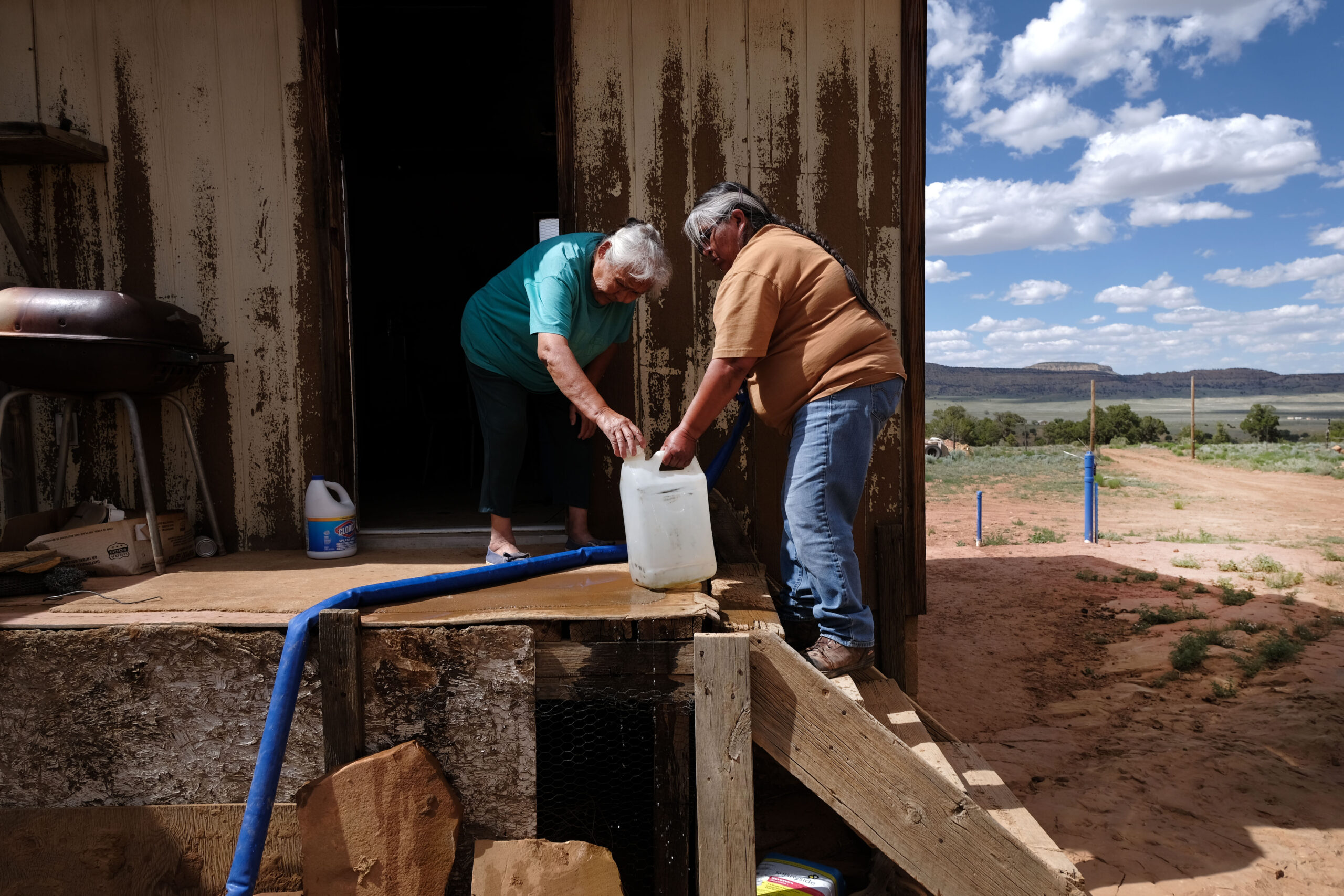 Two older Navajo women with a large plastic water bottle, outside a wooden clapboard house. There is a blue pipe running between them. The rural landscape stretches out into the distance.