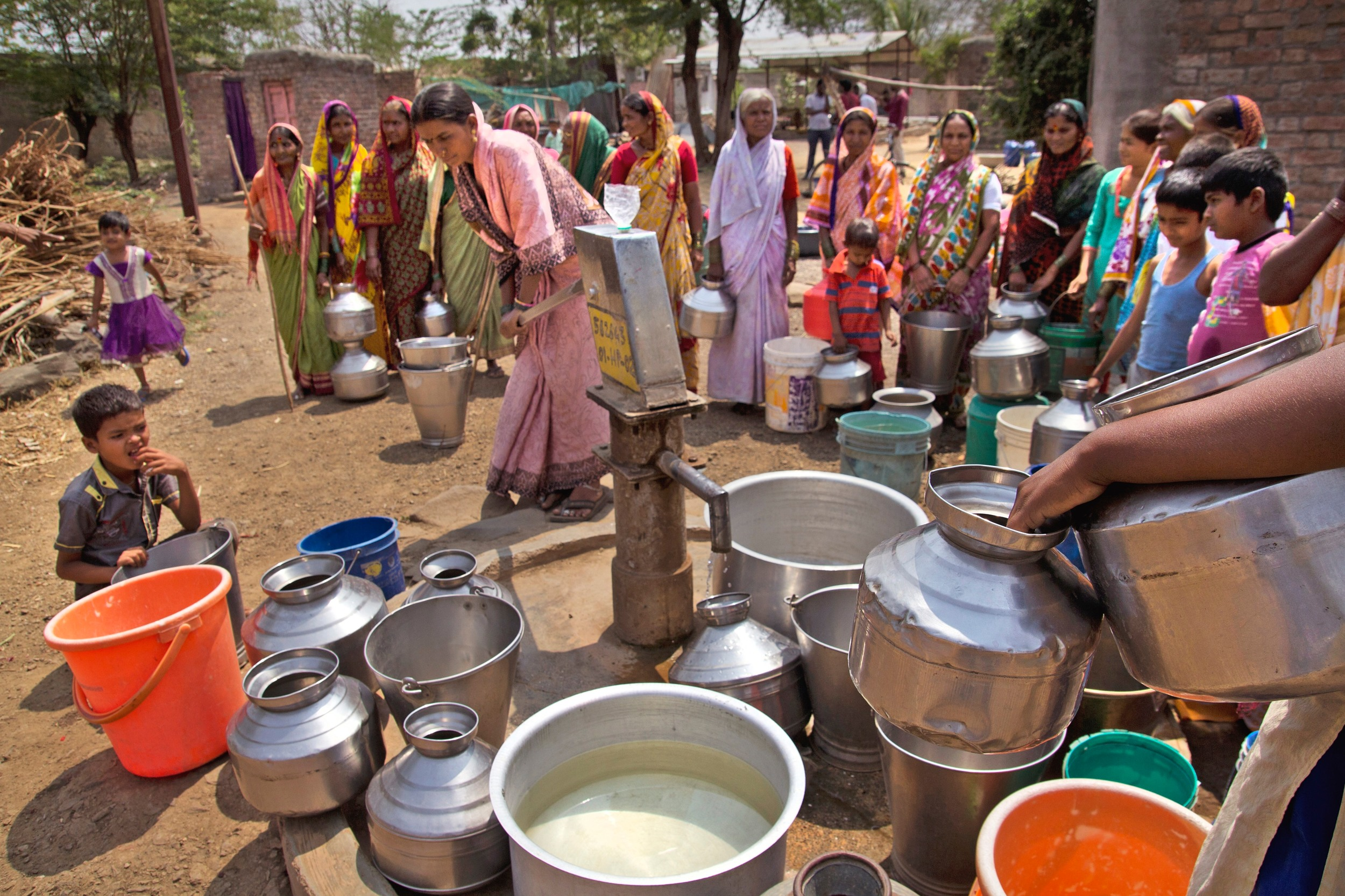 Around 17 Indian village women in colourful saris gather around a single tap in the centre of the frame. There are around 30 containers of water on the ground near the tap and in front of the women, made from metal, plastic and in different shapes and colours and sizes. There are two little children watching closely from the left hand side.