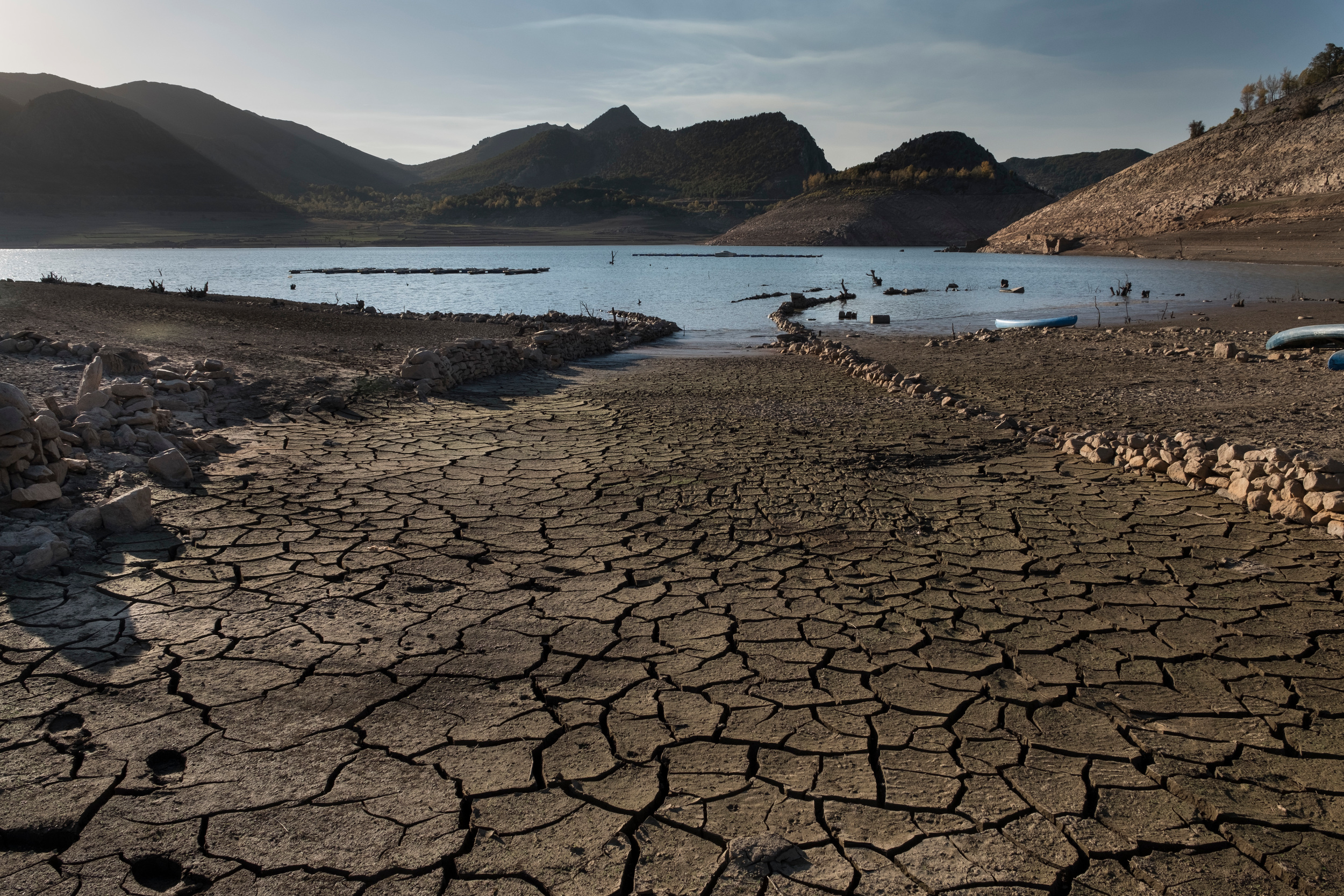 An extremely dried-out, brown landscape with cracked earth in the foreground, with a reservoir in the distance and mountains behind.