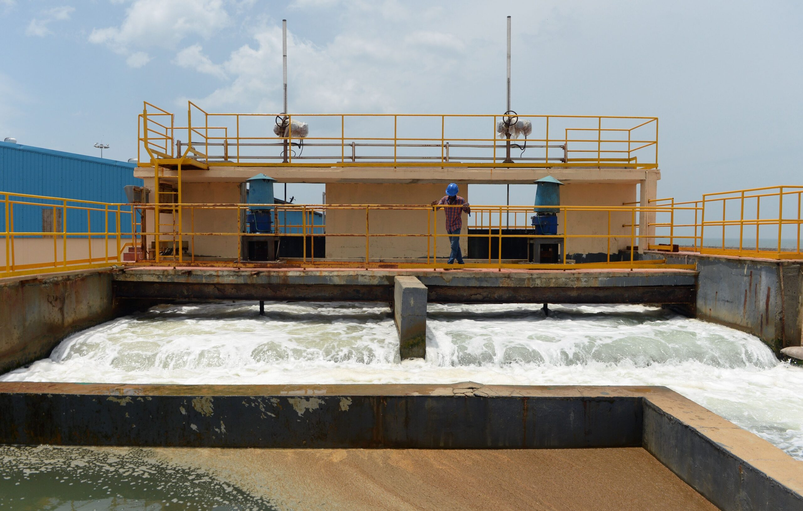 An industrial structure with water running through it. There is a bridge over the running water with a building, lined with yellow handrails and a man standing looking over the water flow.