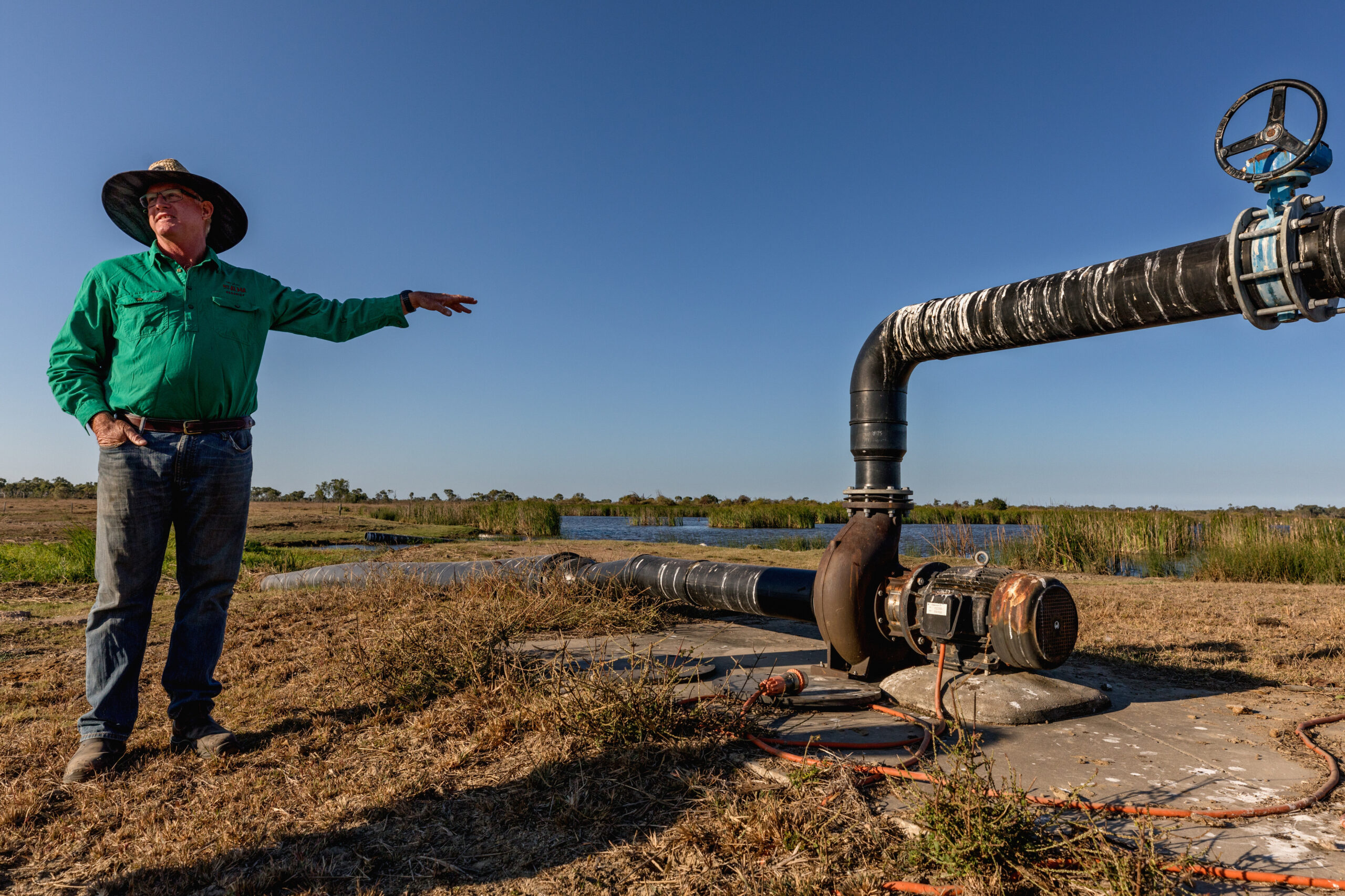 In a dry landscape with little vegetation, backed by a cloudless blue sky, a man stands in blue jeans a green shiry and a cowboy style hat, pointing over to his right, where a large metal pip with a raised section and tap appears to be pumping water to or from the land.