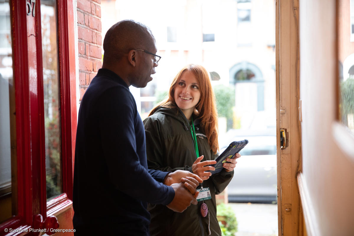 A Greenpeace fundraiser speaks to a potential supporter on the doorstep
