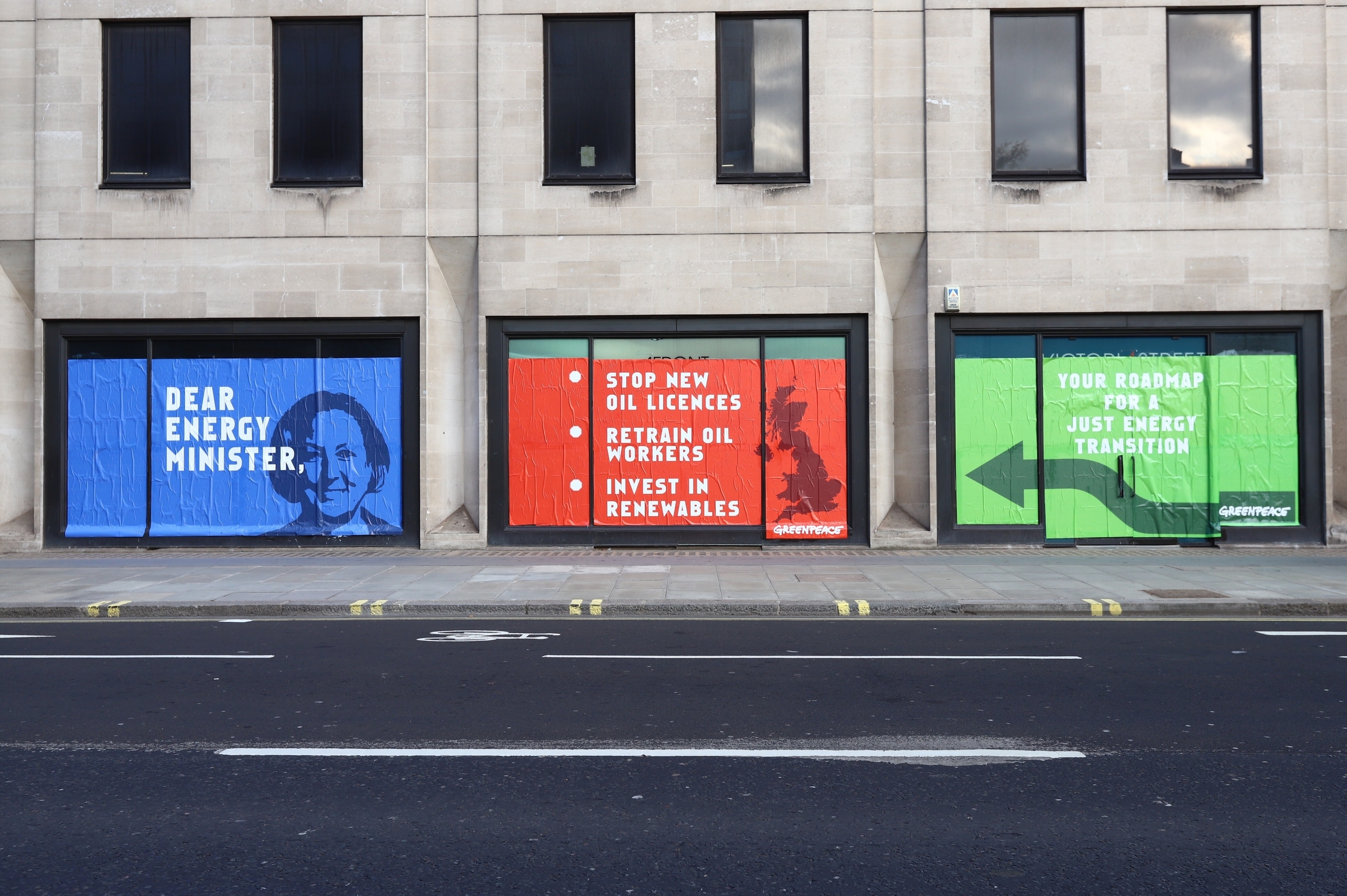 A building with three full-height, long windows plastered with a message to the energy minister. The blue, red and green posters have the energy minister's face, a map of the UK and an arrow on them, and read 'Dear energy minister. Stop new oil licenses. Retrain oil workers. Invest in renewables and the final green poster with the arrow points to the previous list, reading 'Your Roadmap for a Just Energy Transition'
