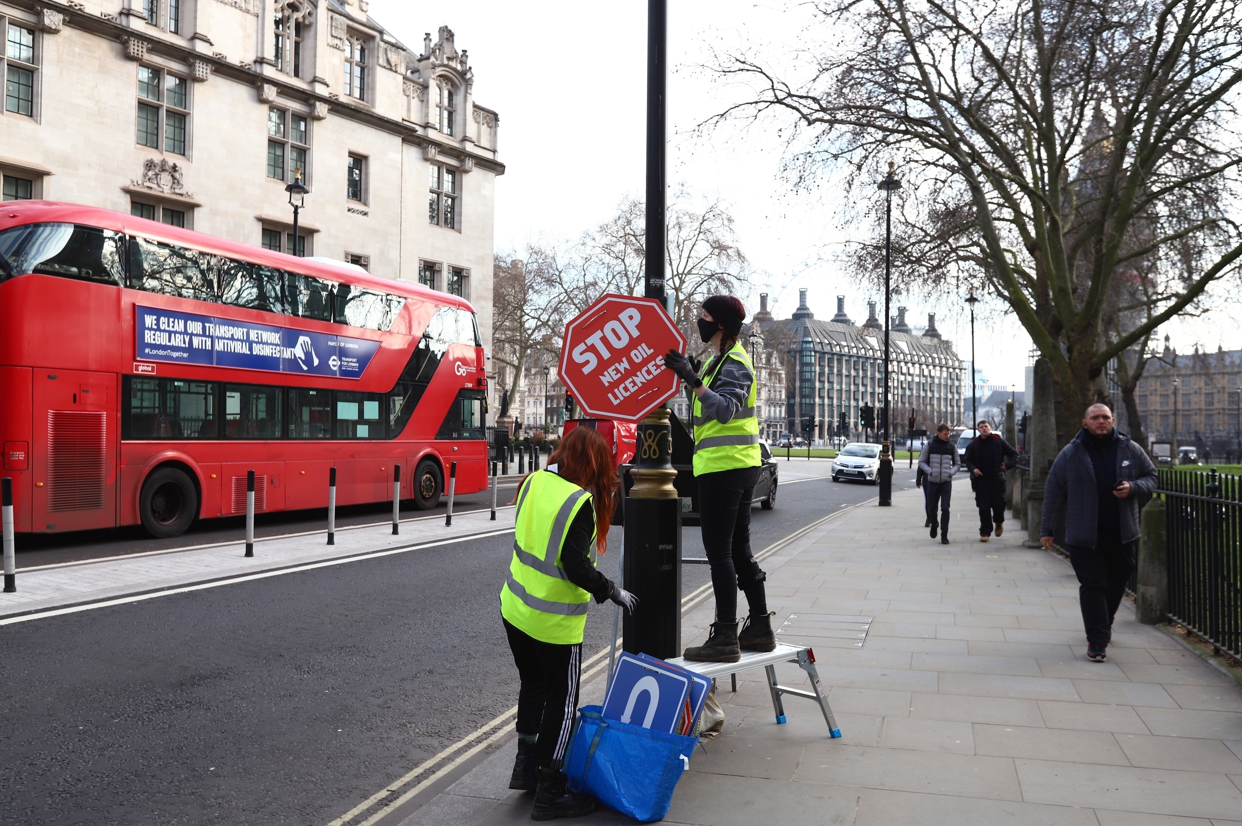 Two women in hi-vis mounting signage on a lamp post. The sign is red and shaped like a stop sign, reading Stop new oil licenses. A red London bus and Parliament Square are in the background.