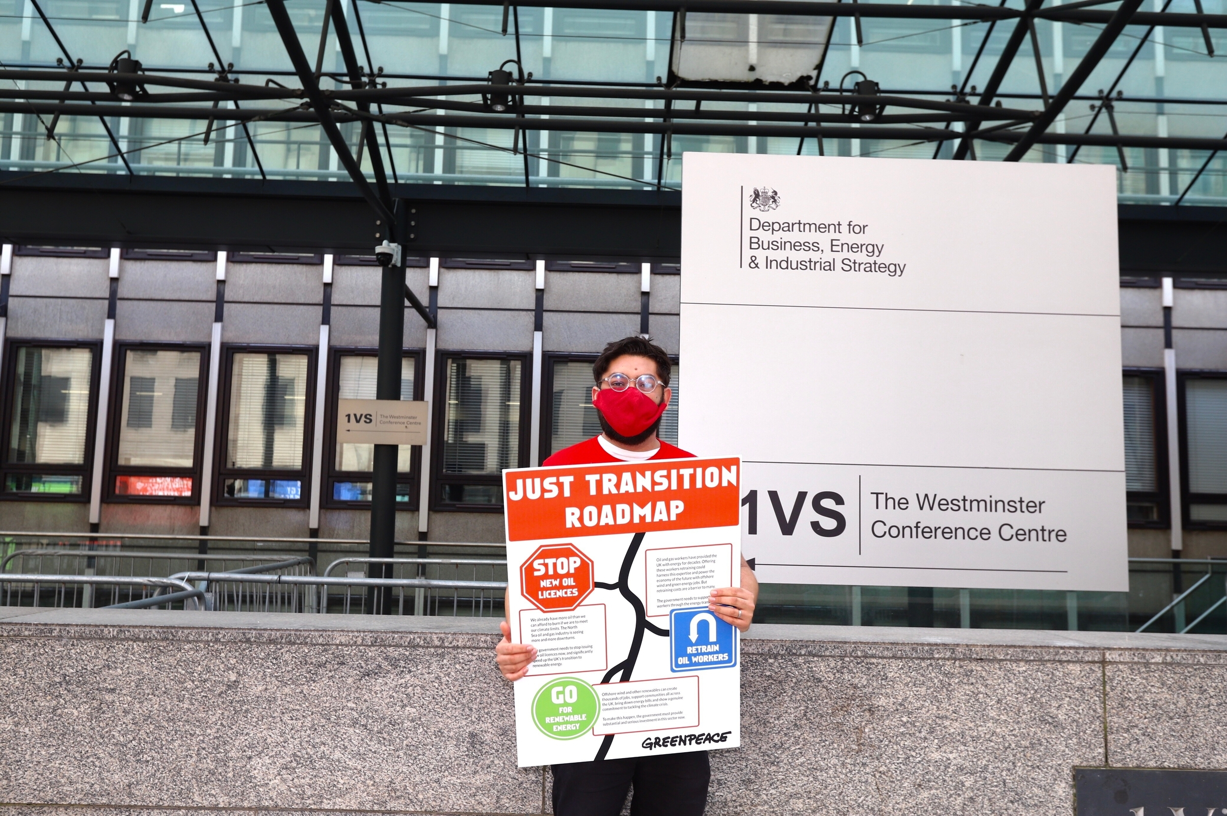 A man stands outside the BEIS department, holding a poster reading 'Just transition roadmap' with 'Stop new oil licenses' and'Invest in renewable energy' on signs that mimic road signs, with arrows in between.'