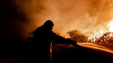 A firefighter sprays water on a blaze, silhouetted against a background of orange smoke