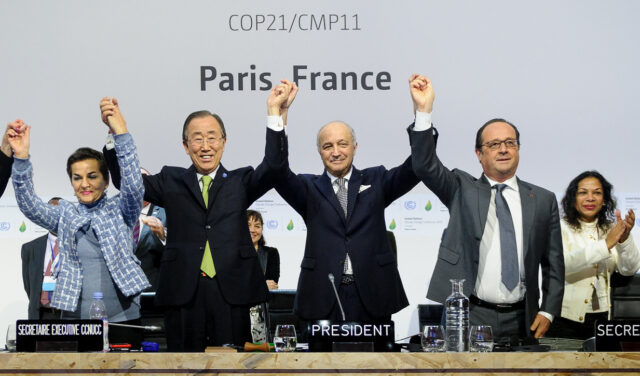 World leaders standing in a line and cheering in front of a United Nations conference backdrop during negotiations for the Paris Climate Agreement