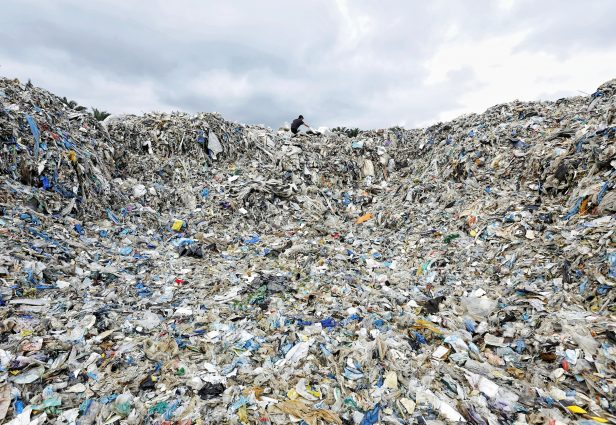 A worker stands at the top of a giant mound of plastic waste