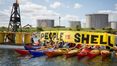 A row of people in colourful kayaks hold up a banner reading 'People vs Shell'