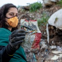 Greenpeace campaigner stands in a waste dump in Turkey, holding up a crisp packet from the UK