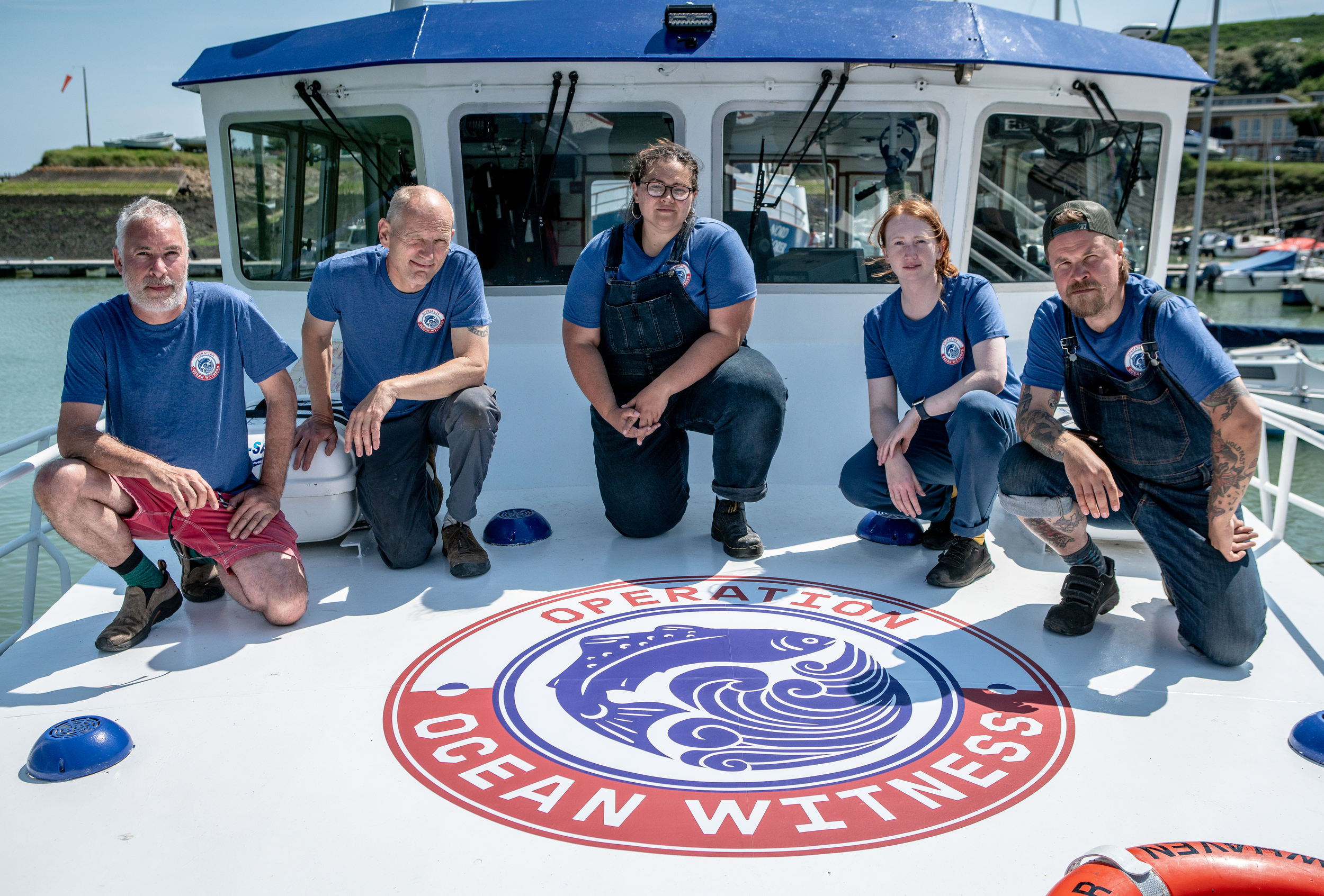 Five crew members kneel on the deck of a small ship in front of a large decal showing the Operation Ocean Witness logo.