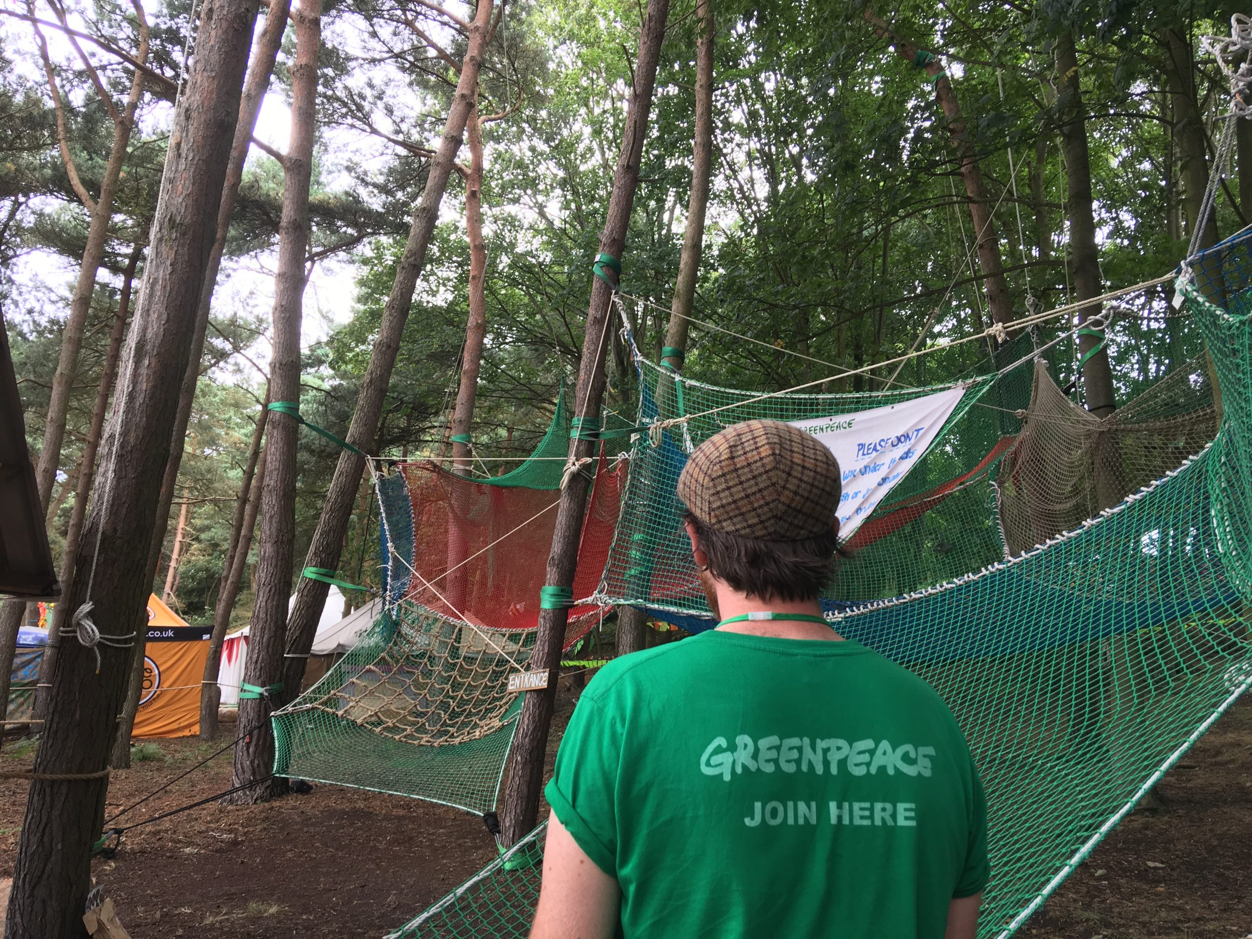 A Greenpeace volunteer stands in front of an obstacle course made of nets attached to trees