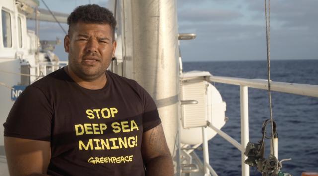 Greenpeace activist Victor wearing a 'Stop deep sea mining' tshirt