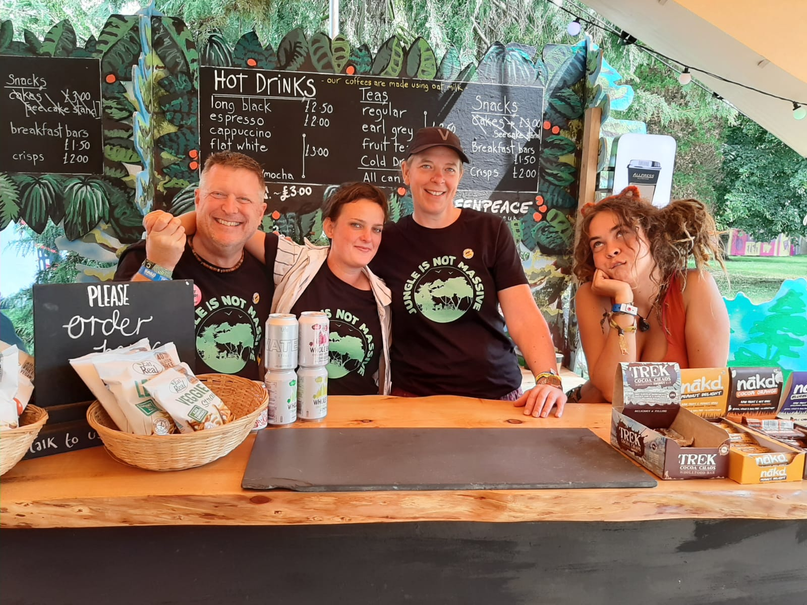 Volunteers in tshirts saying 'Jungle is not massive' operate a refreshments stall with a blackboard menu in the background